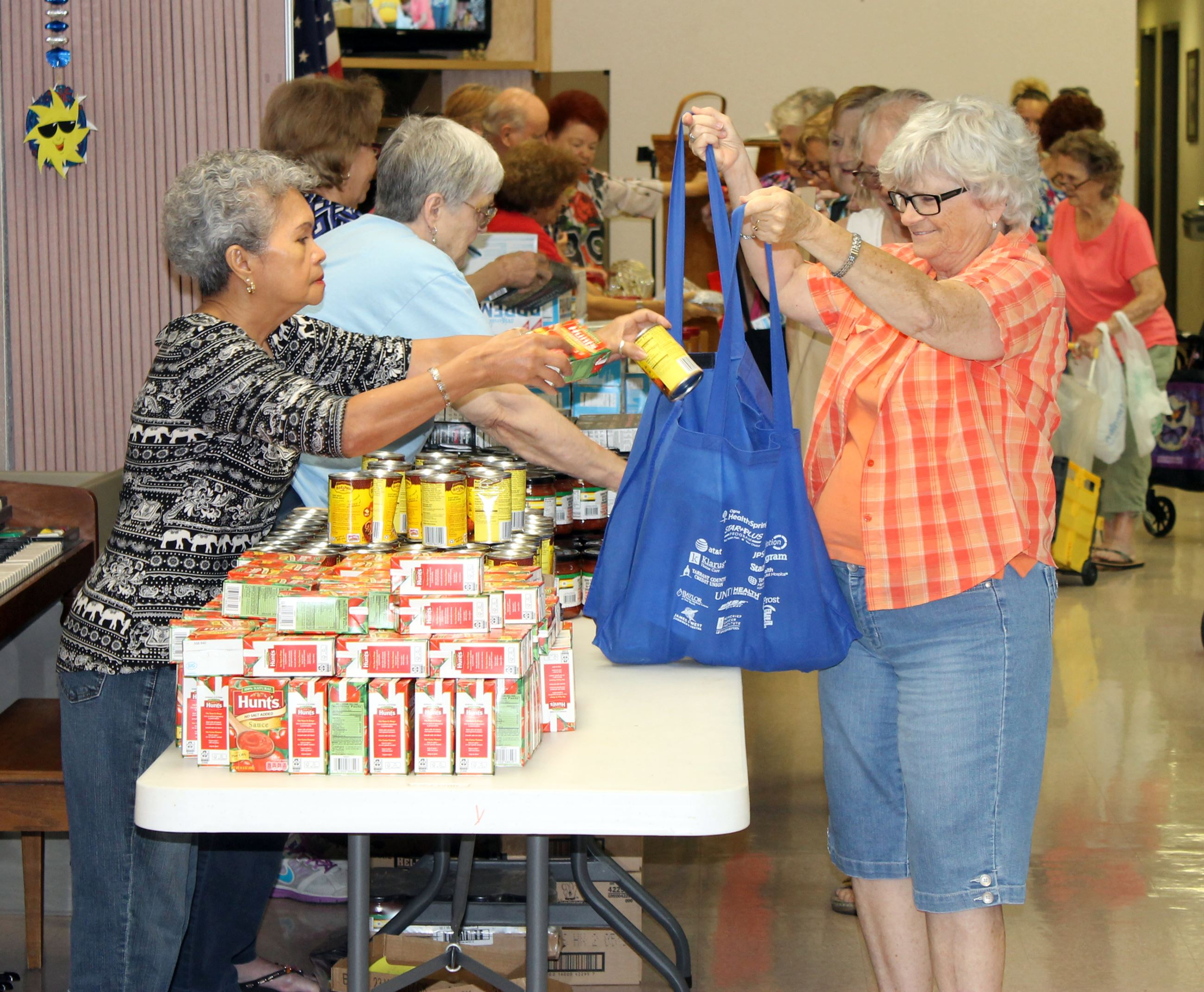 volunteer giving food to senior citizen
